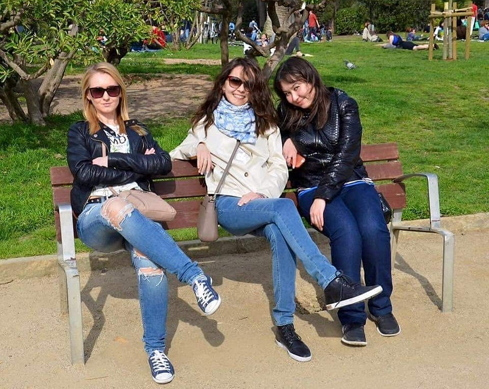 grils sitting in the park - Image Illusion: Can you point out what's strange in the picture ?