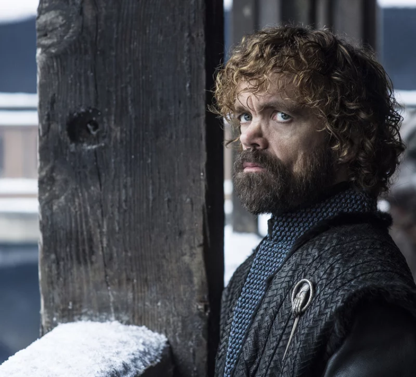Tyrion stand outside Jon and Daenerys' room looking sad and disappointed