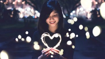 girls holding heart 364x205 - 7 Body Language Hints That They Are Falling For You
