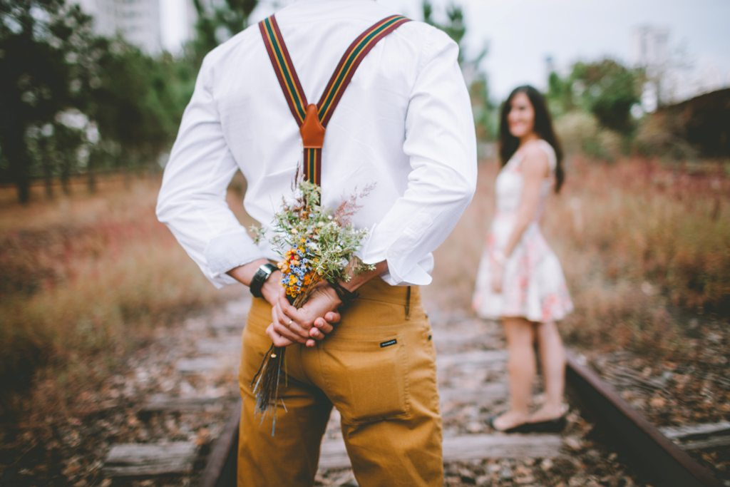 guy holding flowers for girl - 7 Body Language Hints That They Are Falling For You