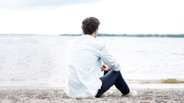 man sitting in front of beach lonely