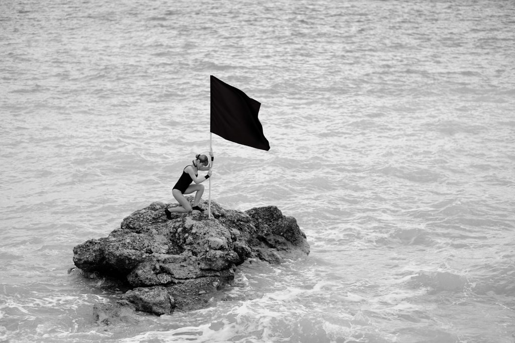 woman putting black flag beach